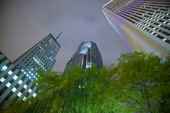 Towering Skyscrapers at Night!. Low angle looking up from the street to the Buildings lit up on with low floating clouds almost touching their tops. Long Stock Photo
