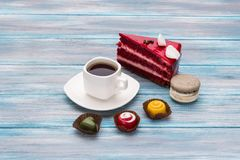 Bright piece of cake beautiful candy and a cup of coffee on a wooden background Stock Images