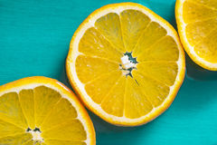 Bright slices of juicy oranges on blue background Stock Images