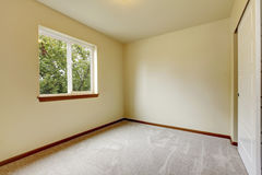 Bright small empty room with carpet floor, one window. Royalty Free Stock Image