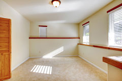 Bright small empty room with closet. Bright empty room with light tones wall, bifold doors closet and carpet floor royalty free stock images