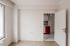 Bright Small Room of New Apartment with One Open Door. Bright small empty room of new apartment with one open door and parquet  floor Royalty Free Stock Photo
