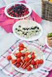 Bright snacks for a picnic with plmidorami cherry, cheese, olives and berries. Olives and cheese, cherry tomatoes with mozzarella and wild berries on a picnic stock photos