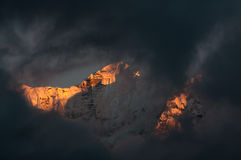 Bright snowy summit through the clouds Royalty Free Stock Photos
