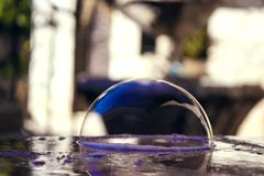 Bright soap bubble on the stone table stock image