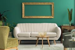 Bright sofa in green interior. Bright sofa standing in green room interior with gold bowl on wooden table, fresh plants and empty frame on the wall royalty free stock photos