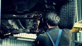 Bright sparks coming from grinder tool cutting rusty worn car parts. stock footage