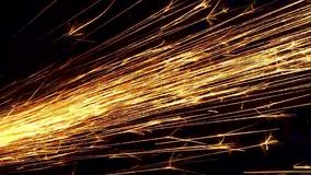 Bright sparks from the grinder shot close-up on a black background. An abstraction of sparks stock footage