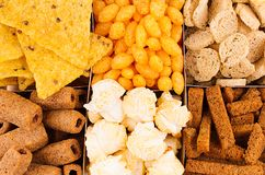 Bright spicy snacks collection - popcorn, nachos, potatoes chips, croutons, corn sticks as chess background. Top view, closeup Royalty Free Stock Photo