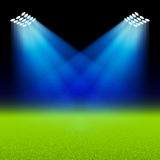 Bright spotlights illuminated green field stadium Stock Images