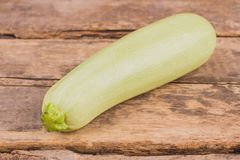 Bright squash vegetable marrow zucchini. Whole pale courgette. Old vintage wooden table background stock images