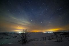 Bright starry night sky above the snowy landscape in the valley. Of the hills stock photos