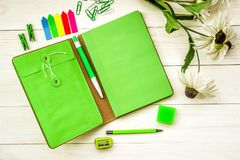 Green creative and stylish stationary set on white wooden background. Bright stationary: natebook, pen,pencil, eraser, sharpener, and stick notes and flowers on Stock Images