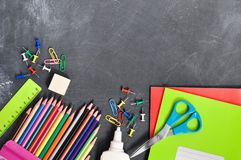 Bright stationery on a black Board background notebooks, pencils, scissors and others. Concept back to school. Top view stock photos