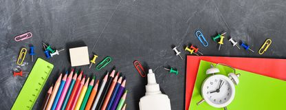 Bright stationery on a black Board background notebooks, pencils, scissors and others. Concept back to school. Top view royalty free stock photos