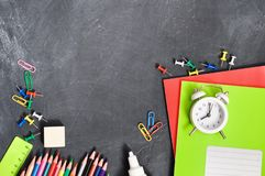 Bright stationery on a black Board background notebooks, pencils, scissors and others. Concept back to school. Top view royalty free stock photography