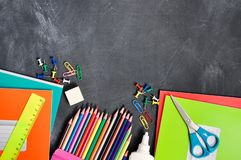 Bright stationery on a black Board background notebooks, pencils, scissors and others. Concept back to school. Top view royalty free stock photo