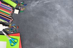 Bright stationery on a black Board background notebooks, pencils, scissors and others. Concept back to school. Top view stock image