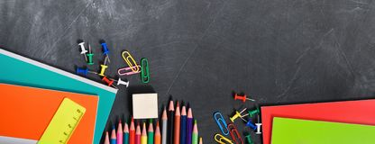 Bright stationery on a black Board background notebooks, pencils, scissors and others. Concept back to school. Top view royalty free stock images
