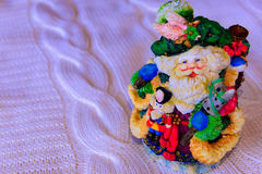 Bright statuette of the grandfather frost cap with bubo. Bright statuette of the grandfather frost in green cap with a bubo is on bazenom the plaid stock image