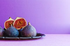 Bright still life organic fig fruits on an old tray, beautiful purple violet background. Selective focus photography, copy space. Bright still life organic fig Royalty Free Stock Image