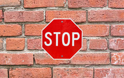 Bright stop sign attached to large brick siding Royalty Free Stock Photos