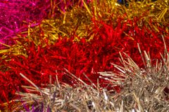 Background of colored tinsel. Bright stripes of shiny tinsel. New Year`s, festive background. Macro photography, artificial lighting Royalty Free Stock Photography