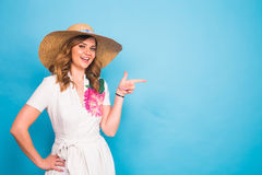 Bright studio portrait of attractive young woman pointing copyspace on blue background. Royalty Free Stock Photos