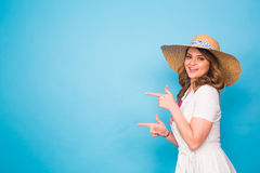 Bright studio portrait of attractive young woman pointing copyspace on blue background. Stock Image