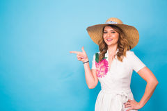 Bright studio portrait of attractive young woman pointing copyspace on blue background. Royalty Free Stock Image