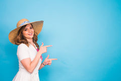 Bright studio portrait of attractive young woman pointing copyspace on blue background. Stock Photography
