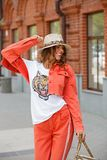Bright stylish girl in an orange denim suit, t-shirt and hat is walking in the city street on a sunny day royalty free stock photo