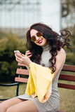 Bright stylish girl sitting on a bench and taking pictures of herself. Excellent Bright Makeup, red puffy lips, long. Dark hair, the girl has fun, goes crazy stock photos