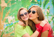 Bright stylish lifestyle urban portrait of two pretty best friends girls in sunglasses. Having fun, kiss and say hello. Two funny stock photos