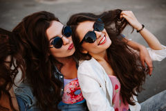 Bright stylish lifestyle urban portrait of two pretty best friends girls posing at denim jackets bright bright pink t. Shirts,long dark hair and sunglasses royalty free stock images
