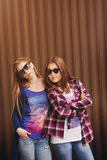Bright stylish lifestyle urban portrait of two pretty best friends girls posing Royalty Free Stock Photography