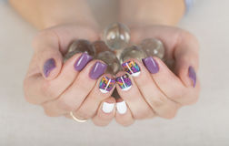 Bright stylish manicure with colored nail gel polish holding glass orbs. Multi colored stylish purple and white manicure Royalty Free Stock Photo