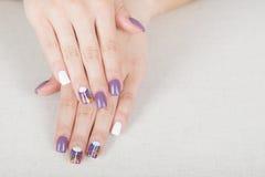 Bright stylish manicure with colored nail gel polish. Multi colored stylish purple and white manicure Stock Image