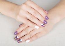 Bright stylish manicure with colored nail gel polish. Multi colored stylish purple and white manicure Royalty Free Stock Photo