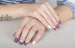 Bright stylish manicure with colored nail gel polish. Multi colored stylish purple and white manicure Stock Images