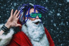 Bright stylish santa. Portrait of a cool punk Santa Claus in luminous glasses with bright dreadlocks over black background royalty free stock photo