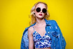 Bright stylish woman. Attractive young woman wearing bright clothes and sunglasses over yellow background. Bright style, fashion. Optics style royalty free stock images