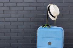 Bright suitcase, hat, glasses, place for text. Blue suitcase, summer accessories stock photos