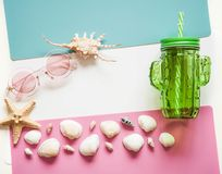 Bright summer background with travel. Seashells, sunglasses, a glass for cocktails on a pink blue white background. Fashionable modern background for summer stock photo