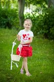 Bright summer berry party in park. Cute girl walking in a park with straw basket Stock Image