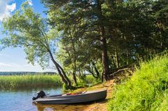 Simple fishers` motorboat, moored to the riparian forest of the lake Seliger under the blinding sunlight, Russia. Bright summer colors of nature, lit by stock photos
