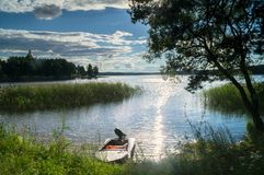 Simple fishers` motorboat, moored to the riparian forest of the lake Seliger under the blinding sunlight, Russia. Bright summer colors of nature, lit by stock photo