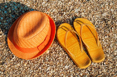 Bright summer hat and sandals on the beach Stock Images