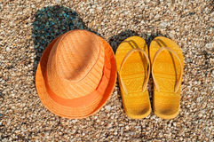 Bright summer hat and sandals on the beach Royalty Free Stock Photography