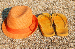 Bright summer hat and sandals on the beach Royalty Free Stock Images